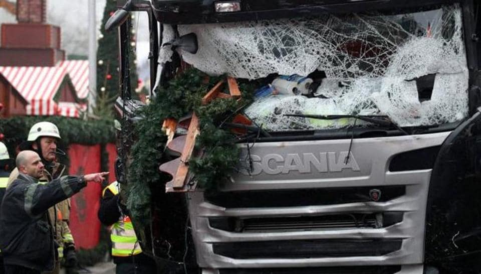 Firefighters stand next to a damaged truck in Berlin. The truck ran into a crowded Christmas market the evening before and killed several people.