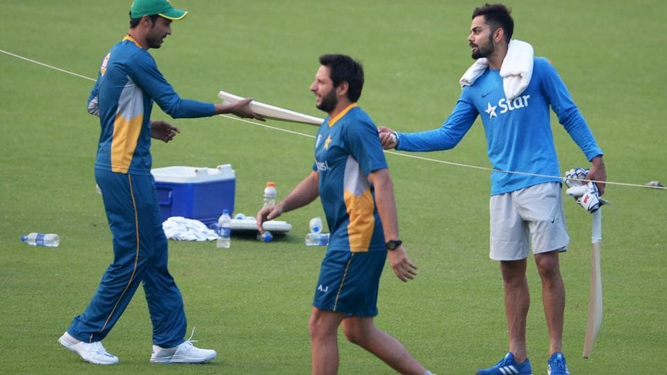 Virat Kohli presents a cricket bat to Mohammad Amir as Pakistan's world T20 captain Shahid Afridi walks past during a training session at the Eden Gardens in Kolkata on March 18, 2016.