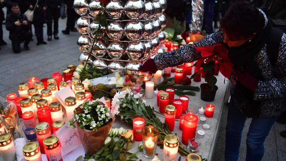 A woman lights a candle at a makeshift memorial on December 20 in front of the Kaiser-Wilhelm-Gedaechtniskirche in Berlin, where a truck crashed  into a Christmas market .