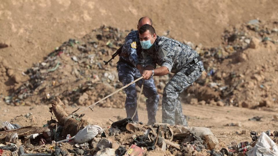 Graphic content / This file photo taken on November 7, 2016 shows members of the Iraqi police trying to pull a body from a mass grave they discovered in the Hamam al-Alil area after they recaptured the area from Islamic State (IS)  Dozens of such sites are discovered in areas around Iraq that have been recaptured from the Islamic State group, whose rule has been defined by extreme brutality.