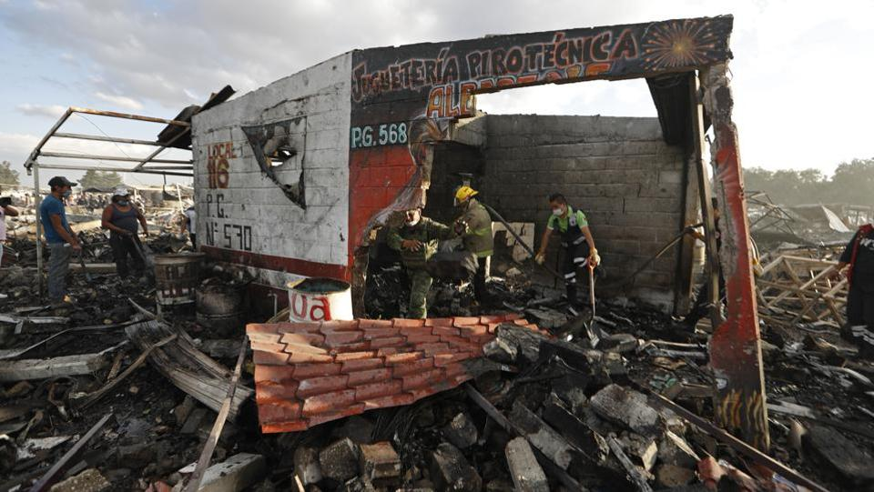 Firefighters and rescue workers remove debris from the scorched ground of Mexico's best-known fireworks market after an explosion ripped through it. (Eduardo Verdugo/AP)