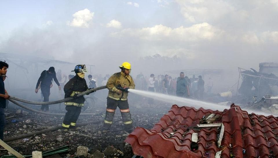 Fire fighters put out smoldering embers amid the debris left by a huge blast that occured in a fireworks market in Mexico City, on December 20, 2016 killing at least 26 people and injuring scores. The conflagration, in the suburb of Tultepec, set off a quickfire series of multicolored blasts and a vast amount of smoke that hung over Mexico City.