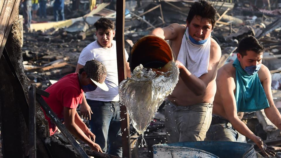 Locals join the rescue workers to douse the embers amid the debris after the blast. (Ronaldo Schemidt/AFP)