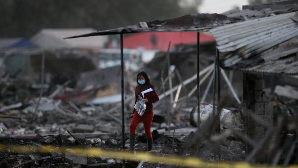A woman walks amid the remains of houses destroyed in an explosion at the San Pablito fireworks market outside the Mexican capital on Tuesday, in Tultepec, Mexico. (Edgard Garrido/REUTERS)