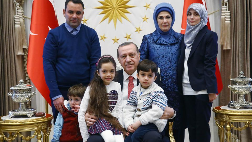 A handout picture taken and released by the Turkish Presidential press office on December 21, 2016 shows Turkey's President Recep Tayyip Erdogan (C) and his wife Emine Erdogan (2nd R) posing with the seven-year-old Bana al-Abed (3rd L), who tweeted from Aleppo on the attacks, and her family, at the Presidential Complex in Ankara.