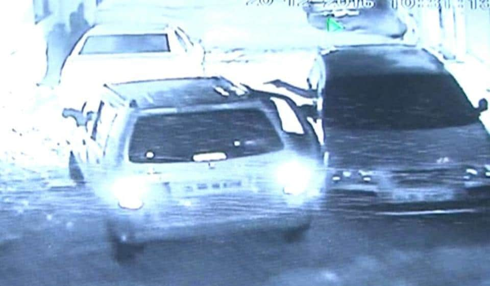 A grab from the CCTVfootage that shows an assailant firing at Brij Bhushan from his car on the right.  Bhushan was a manager a wine shop run by DTTDC.