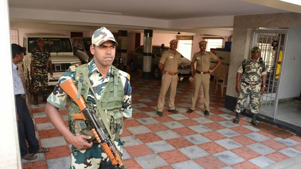 Security forces stand guard as income tax officials raid the home of Tamil Nadu chief secretary in Chennai on Wednesday.