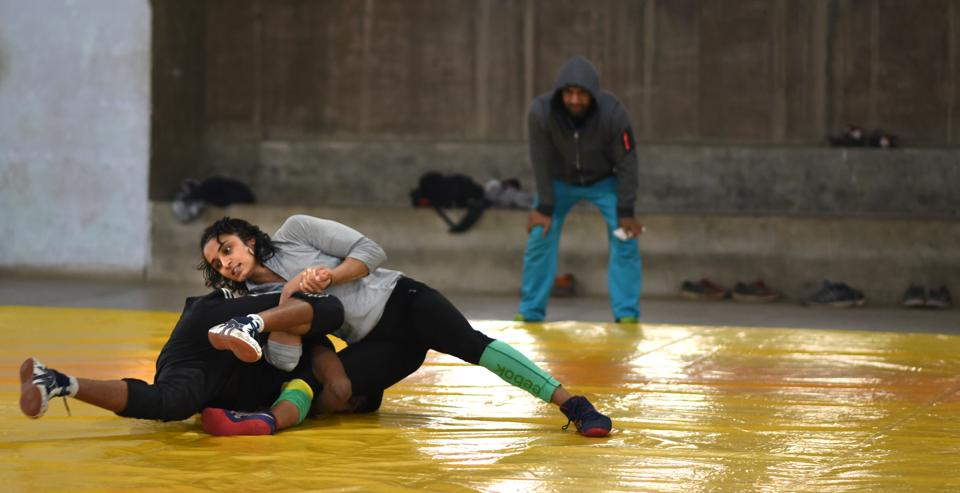 Lalita Sehrawat (above right) wrestles with a male opponent during a practice session in Hisar, Haryana.