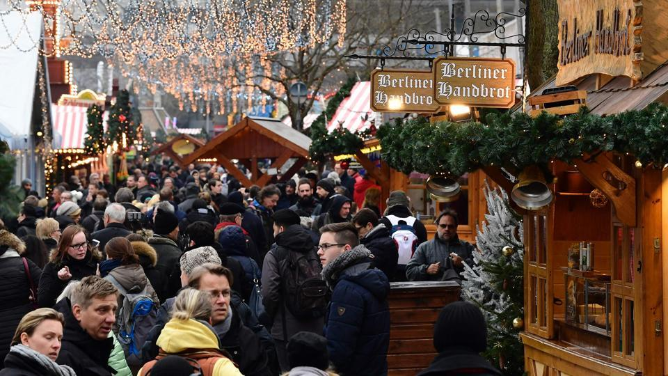 People walk between booths at the Christmas market near the Kaiser-Wilhelm-Gedaechtniskirche (Kaiser Wilhelm Memorial Church) in Berlin on December 22, 2016. The Berlin Christmas market that was struck by a deadly truck rampage on December 19, 2016 reopened, as the grieving city sought a return to normal life and police hunted for the prime suspect in the attack.