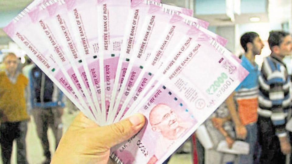 JA bank officer shows new Rs 2000 notes in a bank in Jammu.