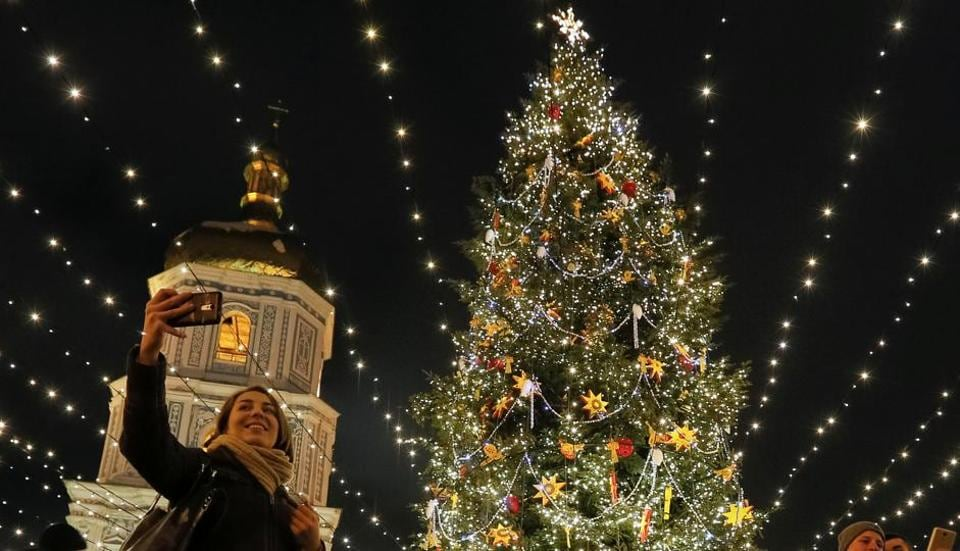 A woman takes pictures next to an illuminated Christmas tree in front of the St Sophia Cathedral in central Kiev, Ukraine. (Reuters photo)