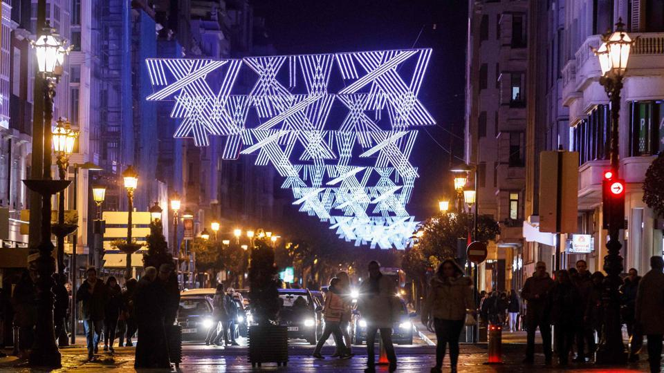 People walk around the Espolon promenade decorated with Christmas lights in Burgos, Spain. (AFP photo)