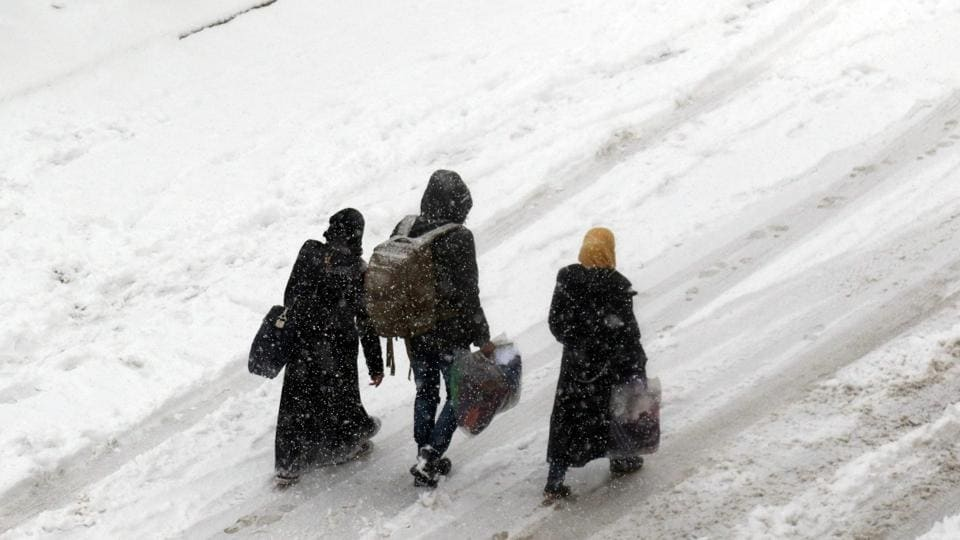 Syrians walk in a snow covered street in the town of Maaret al-Numan, in Syria's northern province of Idlib, on December 21, 2016. At least 25,000 people, including rebel fighters, have left east Aleppo since last week under an evacuation deal that will see the city come under full government control.