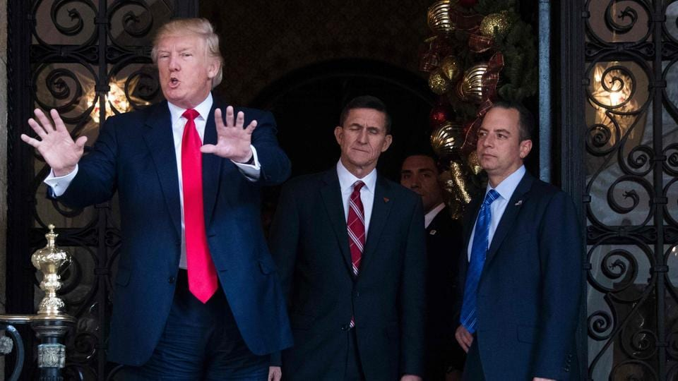 US President-elect Donald Trump (L) gestures as he speaks with Trump National Security Adviser Lt. General Michael Flynn (C) and Trump Chief of Staff Reince Priebus (R) at Mar-a-Lago in Palm Beach, Florida.