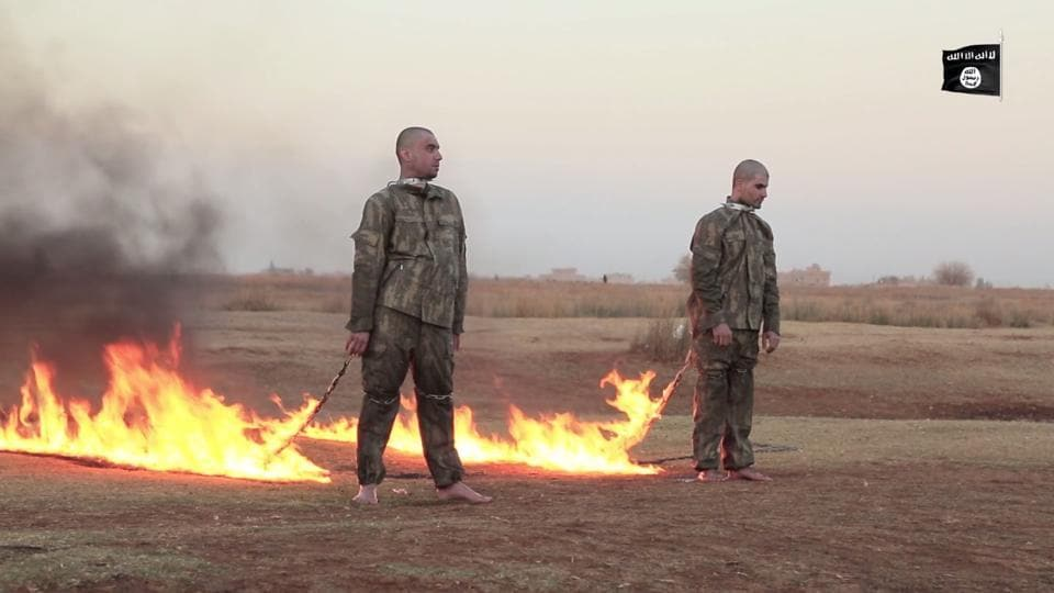 The 19-minute video shows two uniformed men being hauled from a cage before being bound and torched.