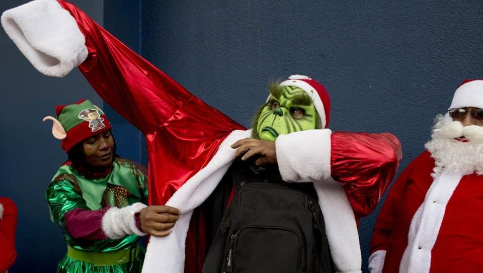 A man is helped to put on his Grinch costume before taking part in the annual Christmas parade in La Paz, Bolivia. Hundreds of people took part in the parade, costumed up as Santa Claus, elves, angels, included floats and marching bands. (uan Karita /AP Photo)
