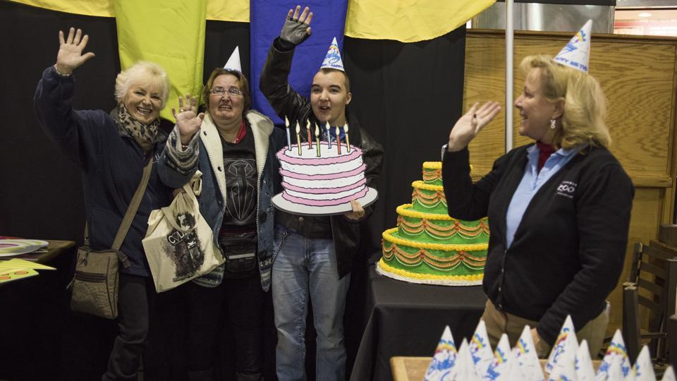 Michele Frymen, from left, Christy Anderson and Jacob Anderson, all from Columbus, hold up a birthday cake and wave as they get their picture taken during some festivities in the food court as part of the 60th birthday celebration for Colo. (AP Photo)