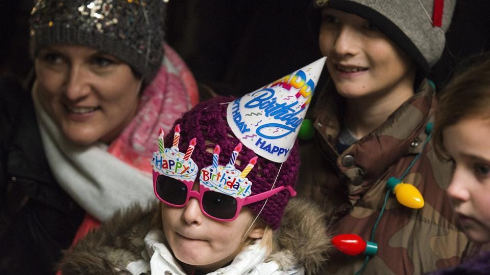 Stella Luken, 5 of Dublin, Ohio, wears a birthday hat and a pair of birthday sun glasses as she waits in line to see Colo. (AP Photo)