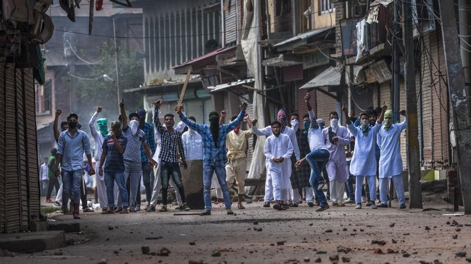 In this photo taken on September 13, 2016, protesters shout slogans and throw stones during clashes with police during a curfew in the Batamloo area of Srinagar.