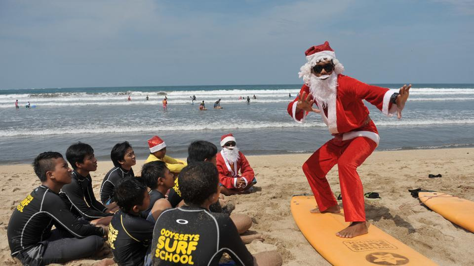 A surfing instructor dressed as Santa Claus gives a lesson to orphans on Kuta Beach, Bali, Indonesia. (Antara Foto/Nyoman Budhiana/ via REUTER)