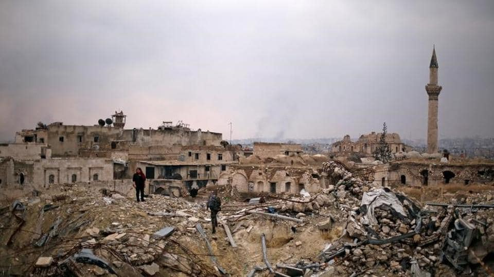 A member of forces loyal to Syria's President Bashar al-Assad stands with a civilian on the rubble of the Carlton Hotel, in the government controlled area of Aleppo, Syria.