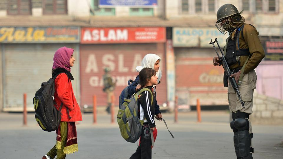 Children walk past paramilitary troopers in downtown Srinagar in November, 2016.