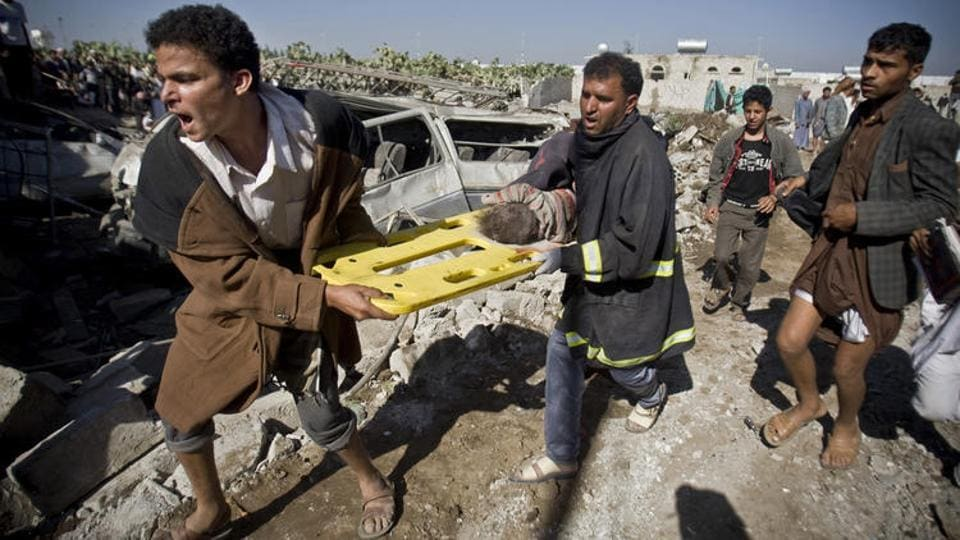People carry the body of a child they uncovered from under the rubble of houses destroyed by Saudi airstrikes near Sanaa Airport, Yemen.