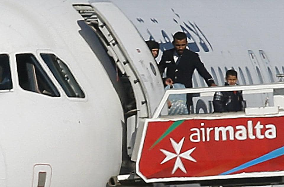 People disembark from a hijacked Libyan Afriqiyah Airways Airbus A320 on the runway at Malta Airport. (REUTERS)