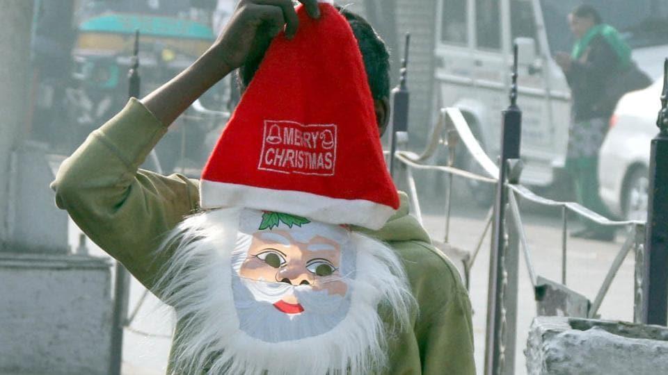 A child selling a Santa mask at Bharat Nagar Chowk in Ludhiana on Friday.