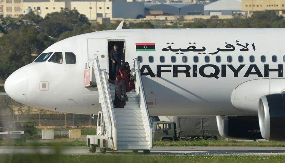 A picture taken on December 23, 2016 in Valletta, Malta, shows a group of hostages being released from the Afriqiyah Airways A320 after it was hijacked from Libya. A man who said he was armed with a grenade hijacked a Libyan plane which landed on Malta Friday with 118 people on board.