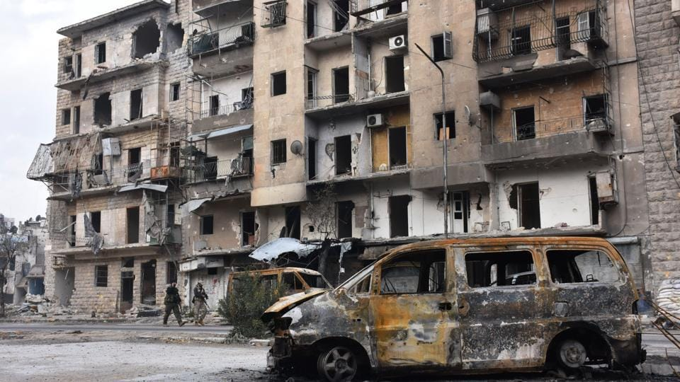 Syrians government forces walk past destroyed buildings in the former rebel-held Ansari district in the northern Syrian city of Aleppo.