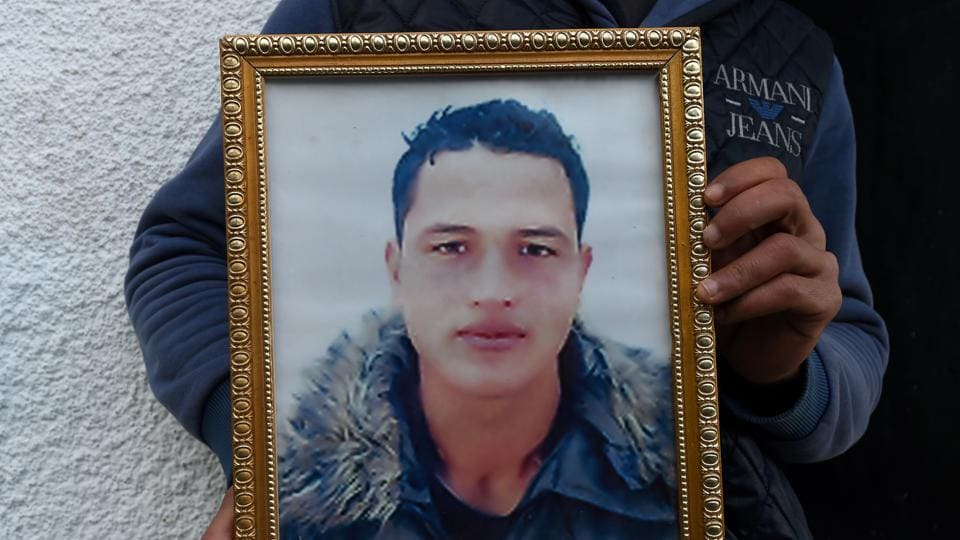 A relative of 24-year-old Anis Amri, the prime suspect in Berlin's deadly truck attack, poses with his portrait in front of the family house in the town of Oueslatia, in Tunisia's region of Kairouan on December 23, 2016.