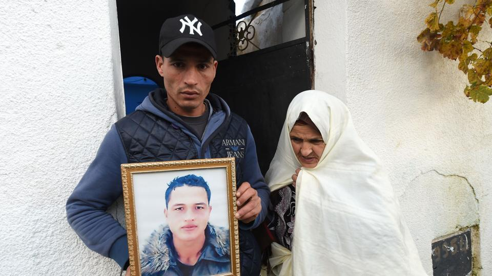 Walid Amri (L), the brother of 24-year-old Anis Amri, the prime suspect in Berlin's deadly truck attack, poses with a portrait of his brother in front of the family house in the town of Oueslatia, in Tunisia's region of Kairouan.