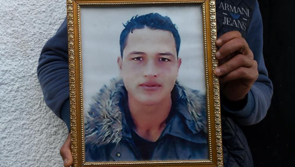 Walid Amri (back), the brother of 24-year-old Anis Amri, the prime suspect in Berlin's deadly truck attack, poses with a portrait of his brother in front of the family house in the town of Oueslatia, in Tunisia's region of Kairouan.
