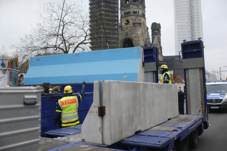 Workers place concrete barriers outside the Christmas market at Breitscheid square in Berlin, Germany, December 22, 2016, following an attack by a truck which ploughed through a crowd at the market on Monday night.