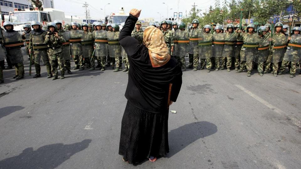 A local woman confronts security forces in Urumqi in China's Xinjiang Autonomous Region. In the region, home to Muslim Uyghurs, restrictions have been put in place on growing a beard and wearing a veil.