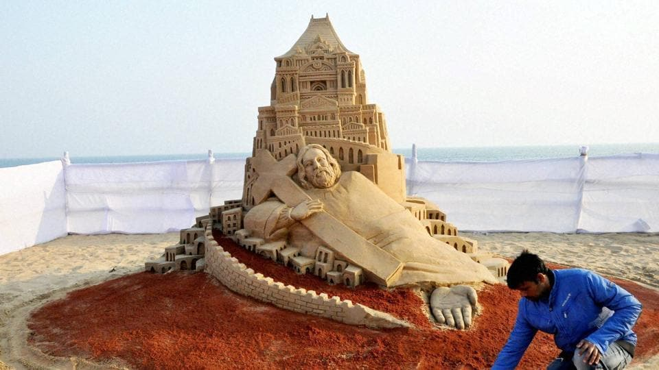 Sand artist Manas Sahoo creates a sand sculpture celebrating Christmas at the beach at Puri in Odisha. (PTI Photo)