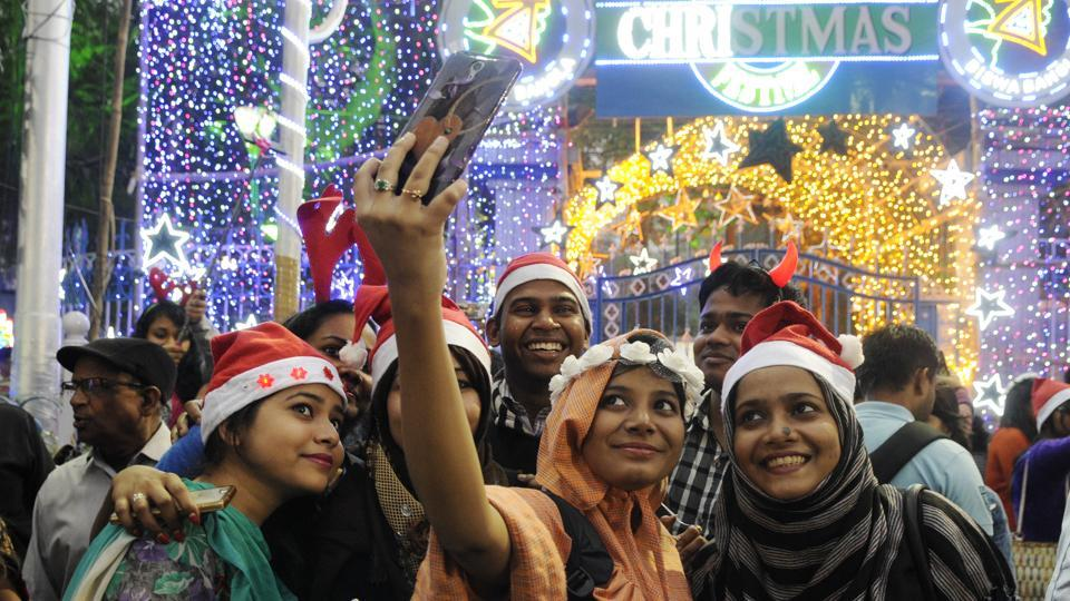 A group of young people take a selfie during Christmas Eve celebration before mid-night mass prayer at Park Street in Kolkata. (Samir Jana/HT Photo)
