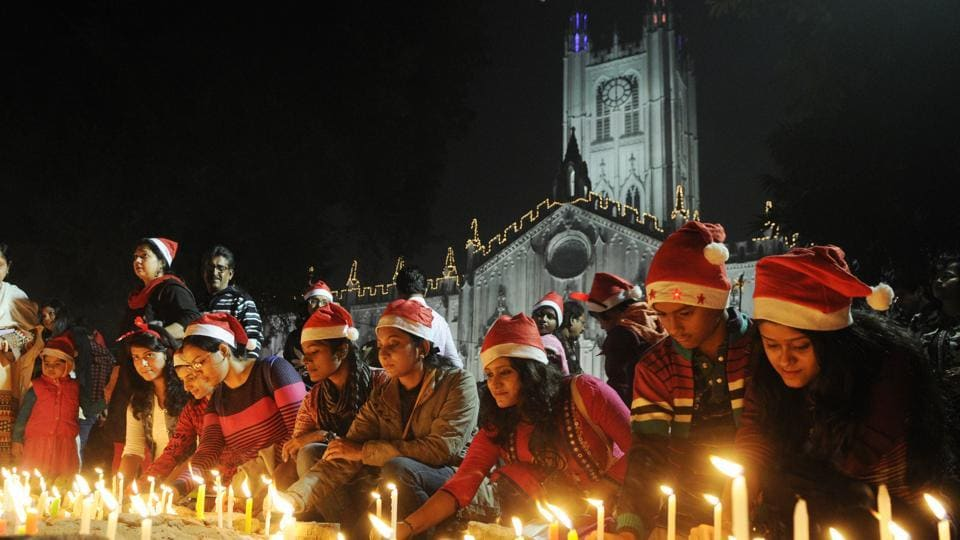 Peoples wearing Santa hats light candles during Christmas Eve celebration in front of St. Paul's Cathedral before Midnight Mass in Kolkata. (Samir Jana/HT Photo)
