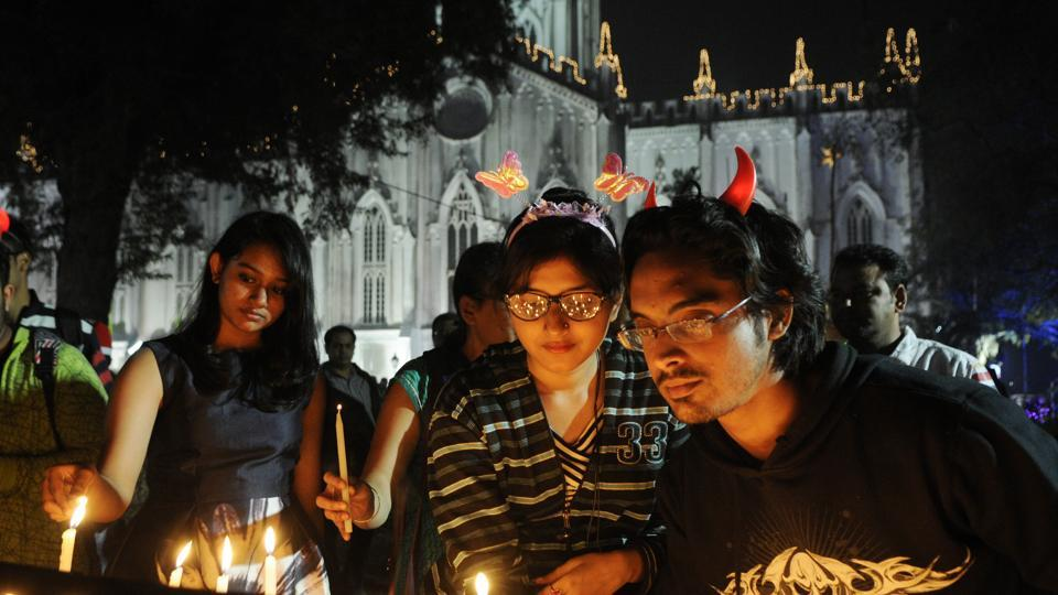 People lighting candles during Christmas Eve celebrations in front of St. Paul's Cathedral before Midnight Mass in Kolkata. (Samir Jana/HT Photo)