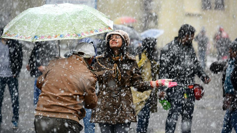 People enjoying the first snowfall of the season at Ridge, in Shimla, on Sunday. (Deepak Sansta/HT Photo)