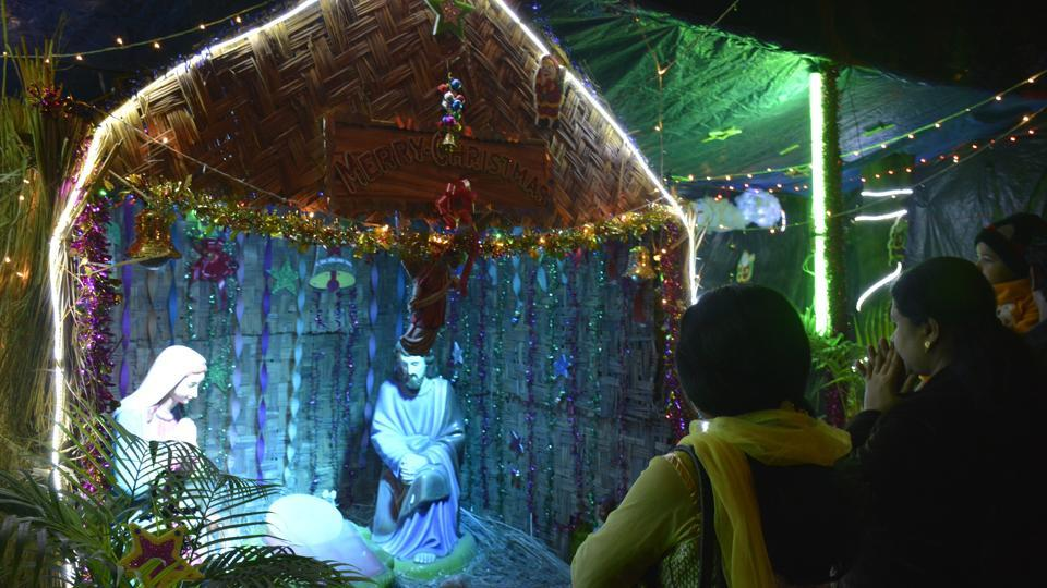 People gather infront of a Nativity scene  in Ghaziabad. (Sakib Ali/HT Photo)