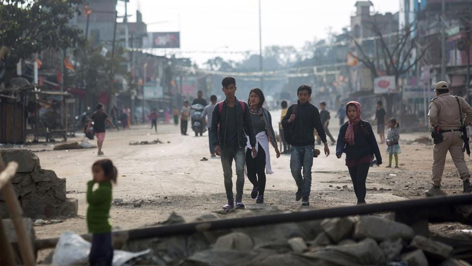 Pedestrians walk past temporary roadblocks on the outskirts of Imphal on December 20, 2016.
