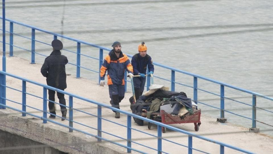 At a quay in the Sochi suburb of Khosta, Russian emergencies ministry members push a cart with remains of Russian military Tu-154 plane which crashed into the Black Sea on Sunday.