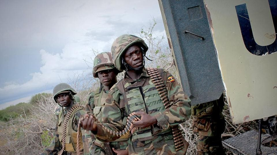 Soldiers with the African Union Mission in Somalia stand next to an armoured personnel carrier during an operation to seize and liberate territories from al Shabaab militants in Deyniile.