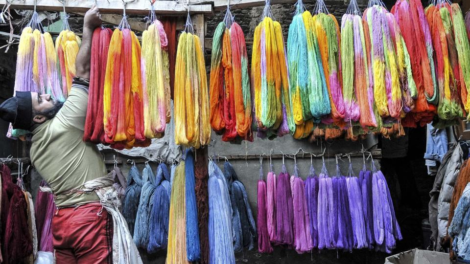 A Kashmiri man adjusts dyed threads as he leaves them to dry. (Waseem Andrabi/HT Photo)