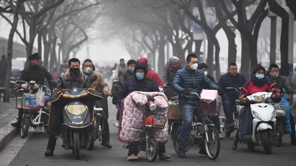 Scooter riders wait to cross a road on a heavily polluted day in Shijiazhuang, in northern China's Hebei province.