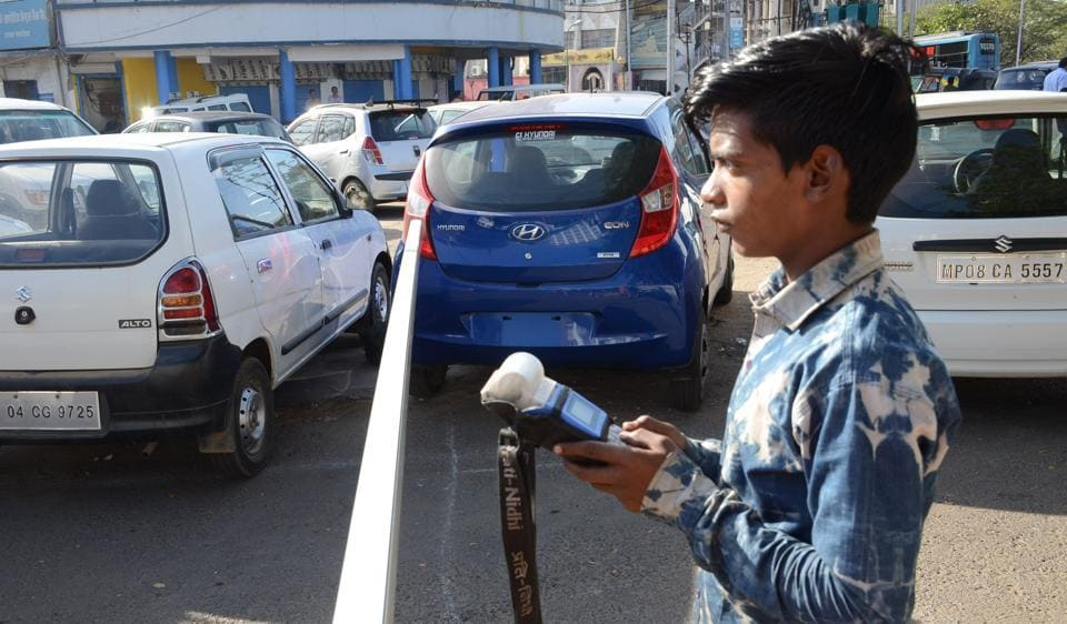 A Bhopal civic body worker uses ticketing machine at a parking lot in the state capital.