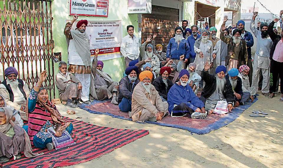 Customers protesting outside Punjab National Bank branch at Dhandra village on Monday.