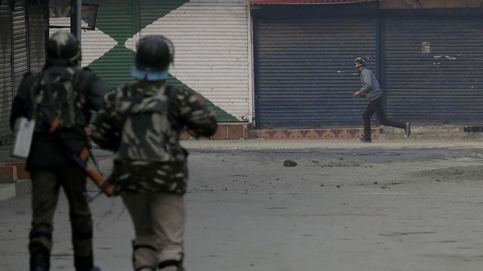 Soldiers chase a protester during a protest after Friday prayers in Srinagar.